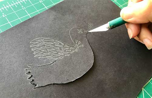 Cutting out dove shadow puppet