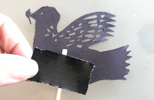 Taping a bamboo stick to dove shadow puppet