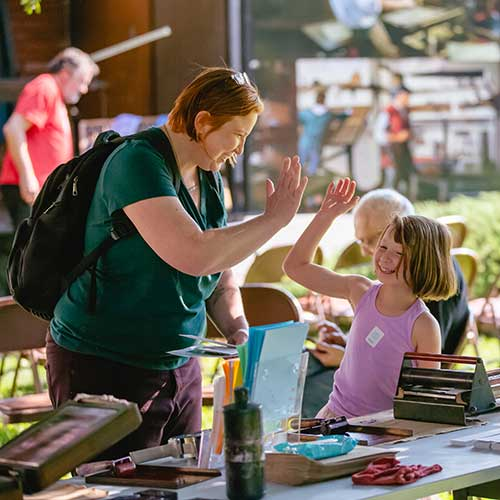 Mom and daughter high-fiving at activity station