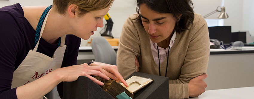 Senior book conservator Andrea Knowlton (left) and Racha Kirakosian, assistant professor of German and the Study of Religion at Harvard University, look at a pear-shaped recess inside the front cover of a 15th-century Dutch codex known as Huntington Manuscript 1048. Photograph by Kate Lain.