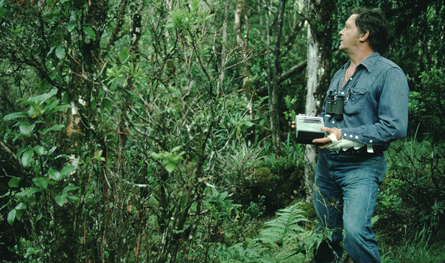 Field biologist John Sincock in the forest with a tape recorder