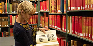 A scholar inspecting a book in the library stacks