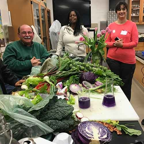 Jim Folsom and participants in his class standing before table with vegetables
