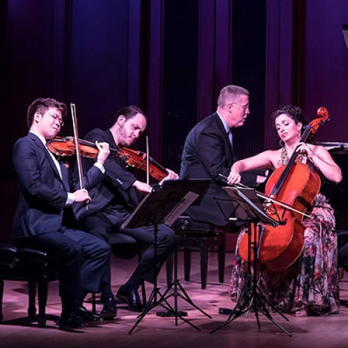 A group of people playing the violin, cello, and piano.
