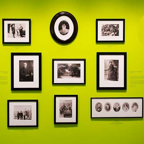 Green wall with black framed photos of the Huntingtons