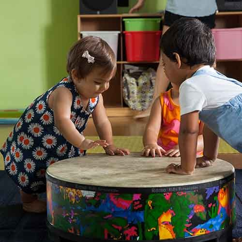 Toddlers playing on a drum