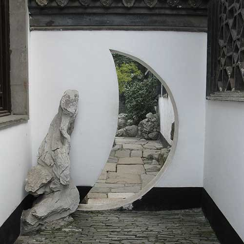 Photograph of crescent moon shaped doorway in a Chinese garden