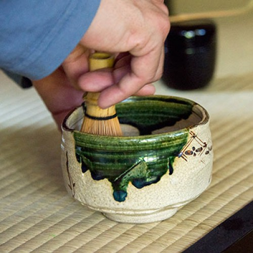 Hand whisking matcha tea in a bowl