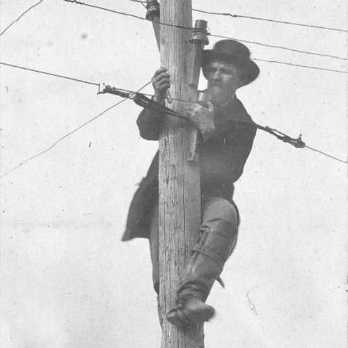 Photograph of man repairing telegraph