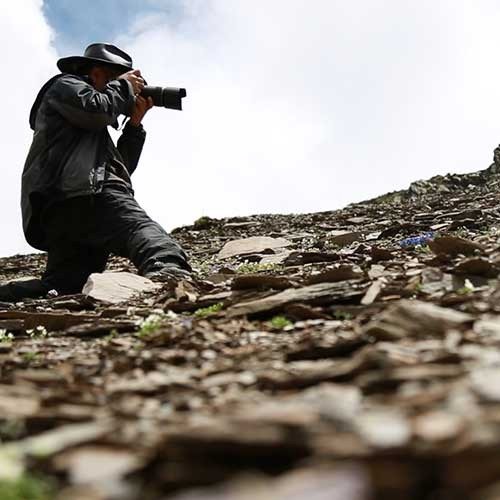 Photographer pointing camera up a mountain