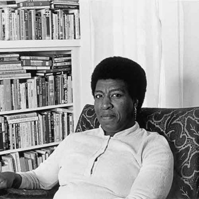 Patti Perret, photograph of Octavia E. Butler seated by her bookcase, 1984. © Patti Perret