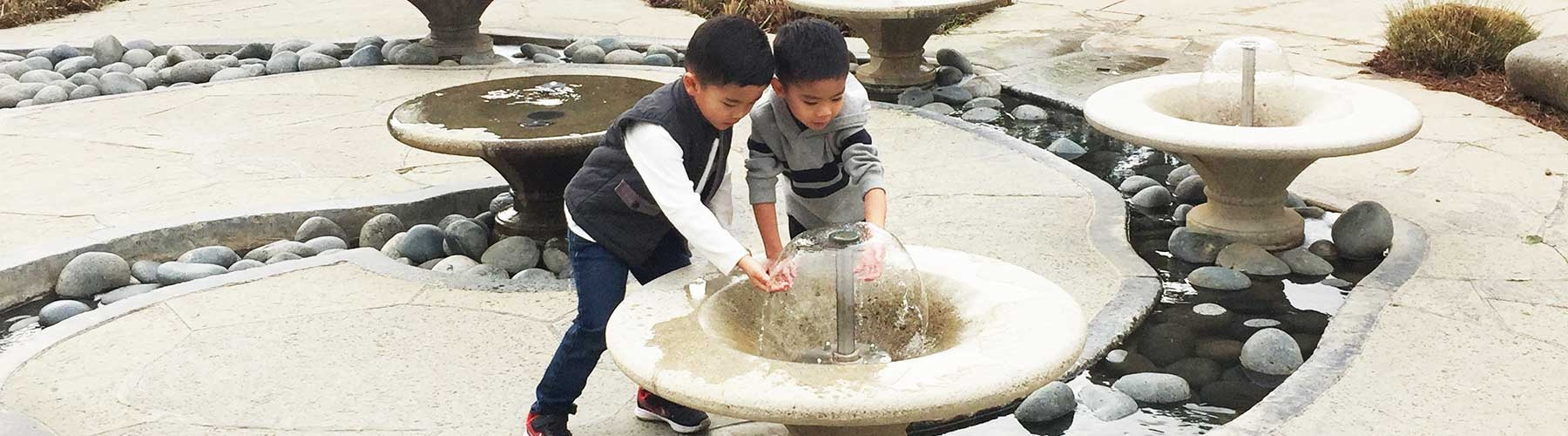 two children playing in a fountain