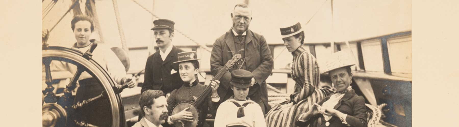 b/w photo of men and women on a ship deck with a banjo