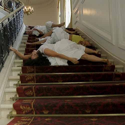 Video still depicting dancers on the staircase in the Huntington Art Gallery, from Apariciones/Apparitions, a video work by Carolina Caycedo.
