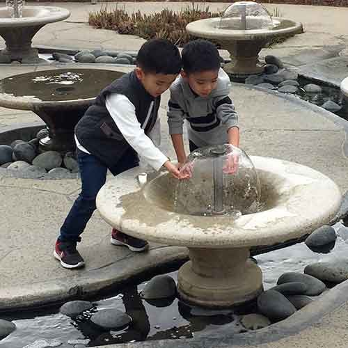 Two brothers playing with water bell