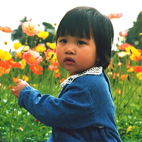 young girl standing in poppies