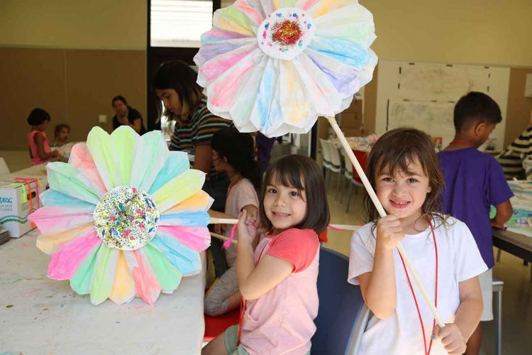 Explorers campers holding giant paper flowers