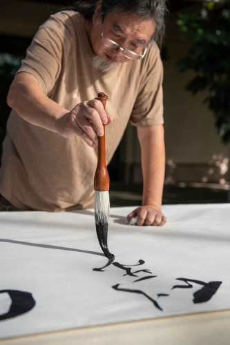 Calligraphy artist Tang Qingnian 唐慶年 at work on a large scroll during a public demonstration in 2018. Tang was the Cheng Family Foundation Artist-in-Residence at The Huntington in 2019. The Huntington Library, Art Museum, and Botanical Gardens. Photo by Jaime Pham