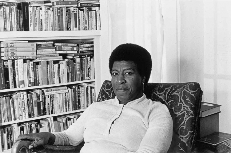 Patti Perret, photograph of Octavia E. Butler seated by her bookcase, 1986. The Huntington Library, Art Collections, and Botanical Gardens. © Patti Perret.
