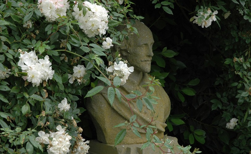 Sculpted bust of William Shakespeare surrounded by white roses