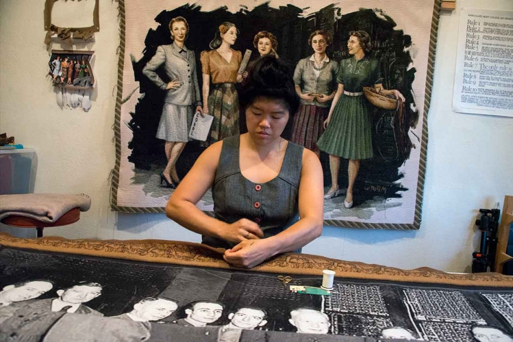 Soyoung Shin stitches a border of one of two tapestries she commissioned while the other hangs on the wall behind her.