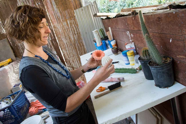 In her outdoor studio, Zya S. Levy peels the latex mold from a plaster cast of a cactus.