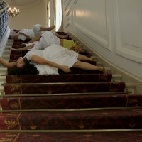 Video still depicting dancers on the staircase in the Huntington Art Gallery, from Apariciones/Apparitions, a video work by Carolina Caycedo. Choreography by Marina Magalhães; cinematography by David de Rozas. Jointly owned by The Huntington Library, Art Collections, and Botanical Gardens and the Vincent Price Art Museum Foundation. Image courtesy of the artist.