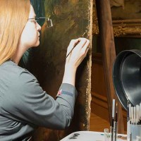 Conservator using tiny brushes to reconnect Gainsborough's brushstrokes