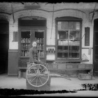 Unknown photographer, Young store clerk sitting in front of shops selling poultry and clothing, Old Chinatown, Los Angeles, ca. 1900. The Huntington Library, Art Museum, and Botanical Gardens.