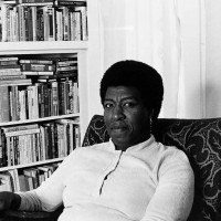 Patti Perret, photograph of Octavia E. Butler seated by her bookcase, 1984.  The Huntington Library, Art Museum, and Botanical Gardens. © Patti Perret