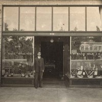 Photo of Fong See standing in front of F. Suie One Co., located on 510 Los Angeles St., ca. 1910s. Unknown photographer. The Huntington Library, Art Museum, and Botanical Gardens.