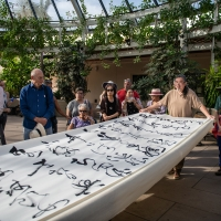 "Tang Qingnian displaying the 40-foot scroll with his transcription of the Tang-dynasty poem, ""Song of Eight Drinking Immortals,"" at a calligraphy demonstration at The Huntington in November 2018. Photo by Jamie Pham. The Huntington Library, Art Collections, and Botanical Gardens"