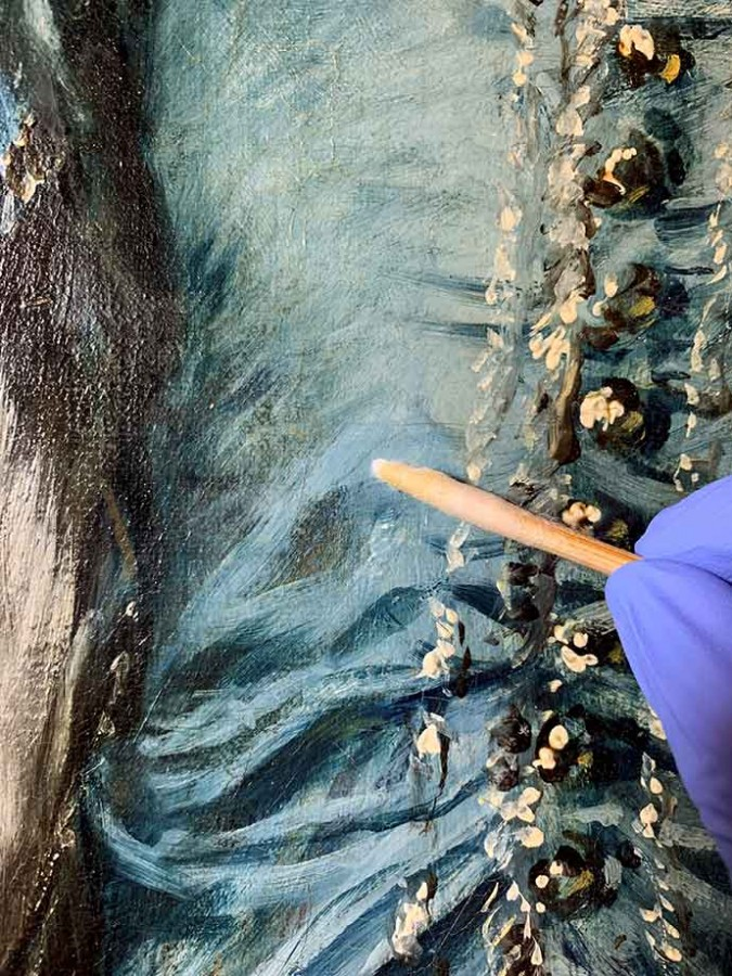 The conservator removed yellowed and cloudy varnish with small cotton swabs to reveal Gainsborough's brilliant blues, visible in the lower portion of the photo. The Huntington Library, Art Museum, and Botanical Gardens.