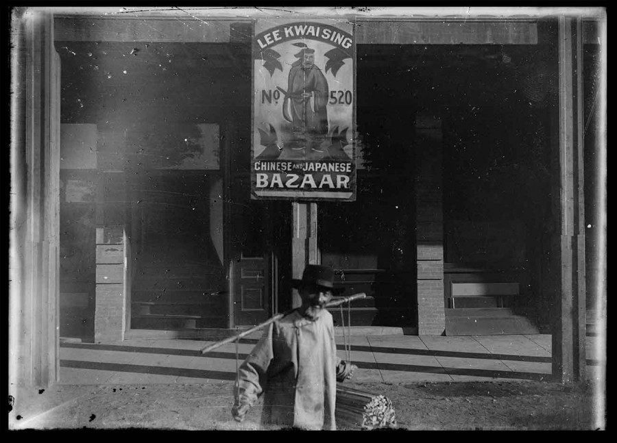 Unknown photographer, Chinese street peddler standing in front of the Lee Kwai Sing shop, Old Chinatown, Los Angeles, ca. 1900. The Huntington Library, Art Museum, and Botanical Gardens.