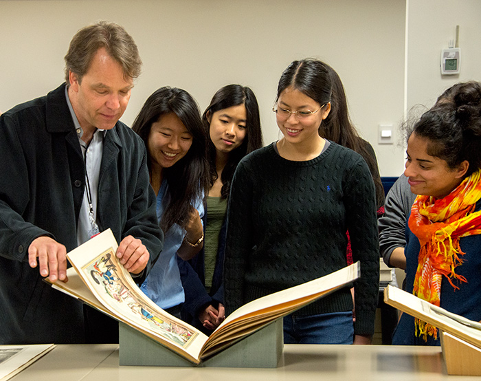 "During a visit to The Huntington, Caltech professor Kevin Gilmartin shows his English 127 students a book illustrating ""monstrosities of fashion."" Photo by Kate Lain."