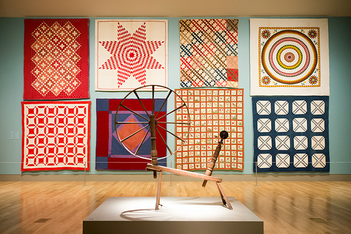 This selection of quilts, made between 1850 and 1900, includes a wide variety of styles and patterns. The spinning wheel in the foreground dates from the early 18th century. Jonathan and Karin Fielding Collection. Photo by Kate Lain.