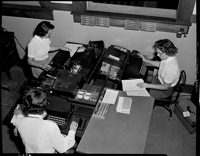 Edison photographer Doug White's overhead shot of three computer key punch operators creating data entry cards, undated. Southern California Edison Archive. The Huntington Library, Art Collections, and Botanical Gardens.