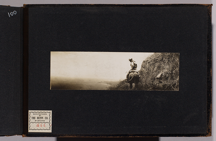 Charmian London on horseback at Molokai pali (cliff) with Kalaupapa peninsula visible in the distance, July 1907. Jack London Collection. The Huntington Library, Art Collections, and Botanical Gardens.