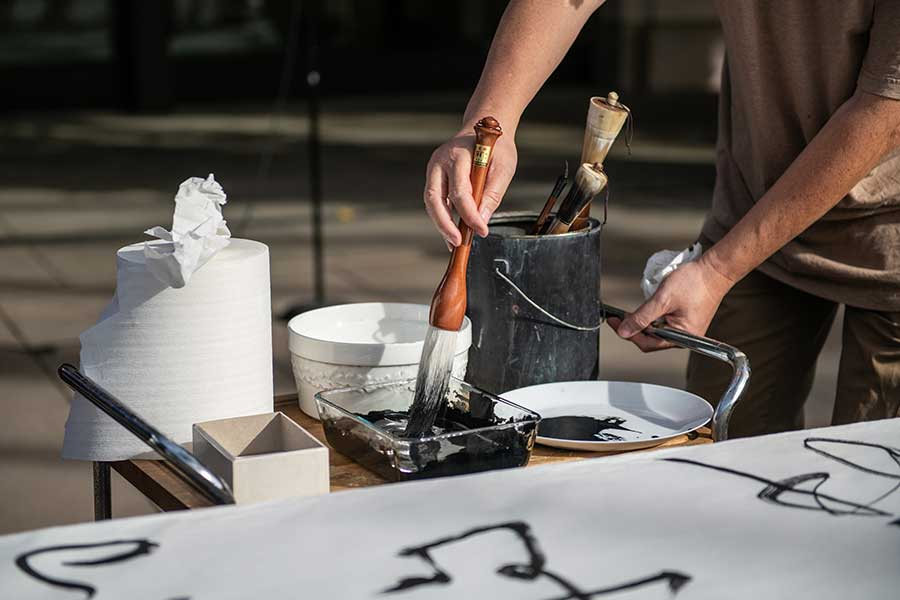 Tang Qingnian dips his brush into ink. Photo by Jamie Pham.