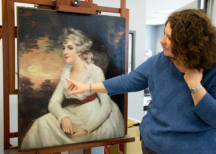Melissa Gardner, associate conservator of paintings at the Museum of Fine Arts Houston, points toward a problematic area on the surface of The Huntington's Lady Elizabeth Crichton, later Viscountess Mount-Stuart (ca. 1791), after Henry Raeburn. Photo by Deborah Miller.