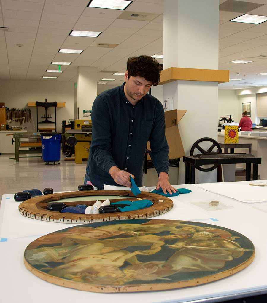 Jose Luis Lazarte, research scholar in paintings conservation at The Metropolitan Museum of Art in New York City, applies small weights to the back of an oil study, Sphinx and Chimaera (1916–1921), by John Singer Sargent, to address the canvas's undulation issues. Photo by Deborah Miller.