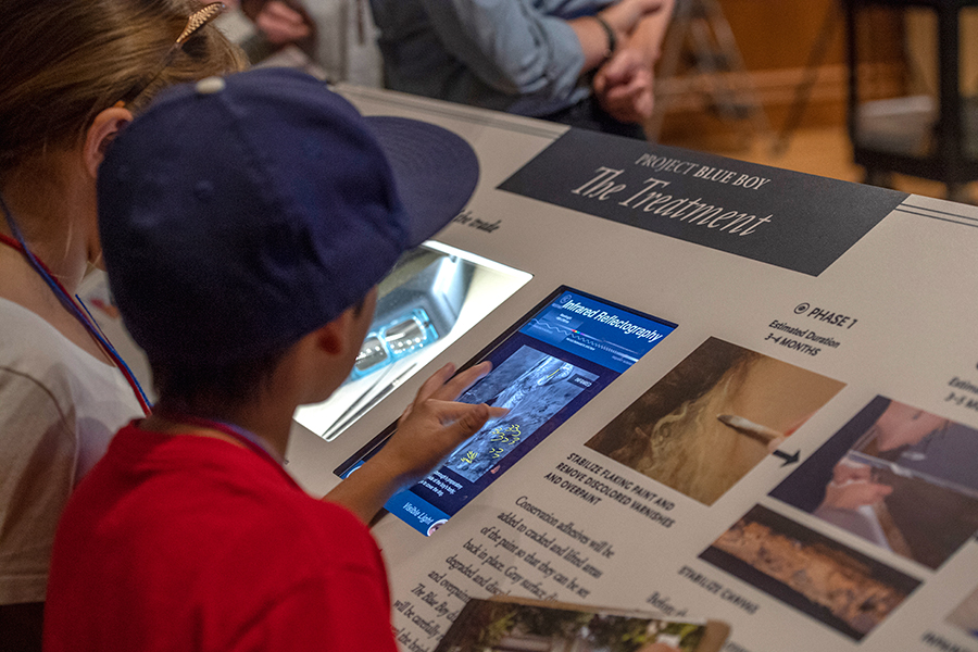 Student interacting with the infrared refractology image of The Blue Boy on a display in the Thornton Portrait Gallery. Photo by Martha Benedict.