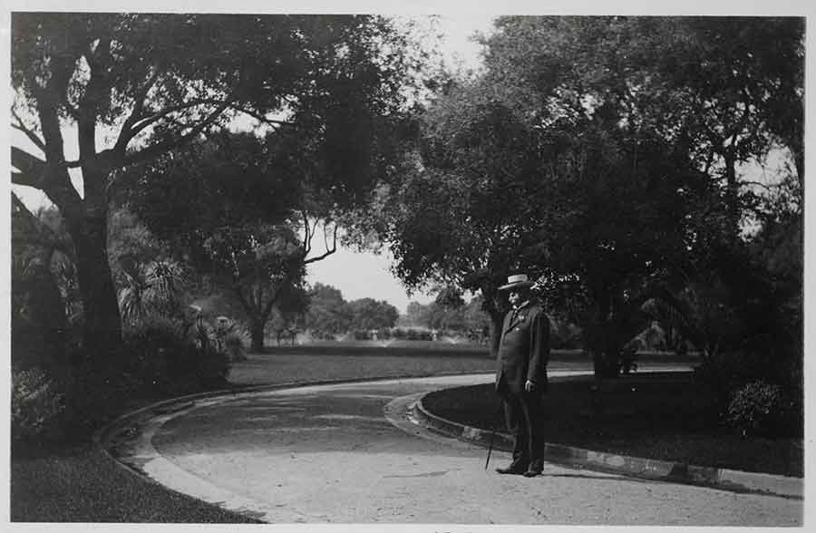 Henry E. Huntington (1850–1927), in about 1915, standing with the North Vista in the background. The Huntington Library, Art Museum, and Botanical Gardens.