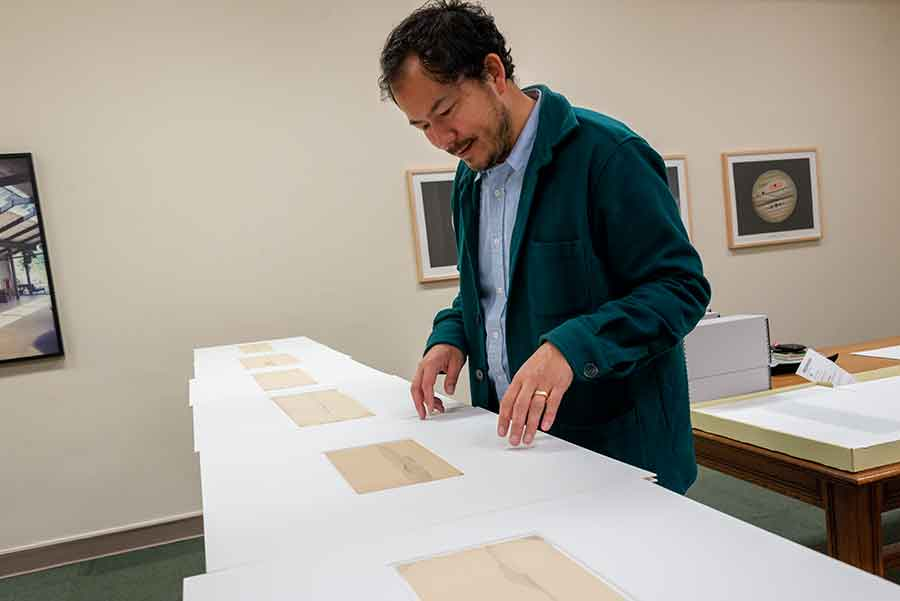 Rosten Woo studies landscape drawings produced during an expedition led by John Russell Bartlett (1805–1886). Bartlett was hired to draw the border between Mexico and the United States after the Mexican American War in 1846. Photo by Kate Lain.